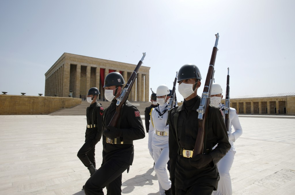 Turkish honour guard soldiers wearing face masks for protection against the new coronavirus, walk during a ceremony at the mausoleum of Mustafa Kemal ...