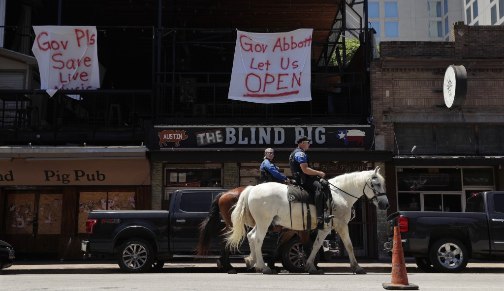 Austin police officers on horseback pass signs hanging on a pub directed at Texas Gov. Greg Abbott in Austin, Texas, Monday, May 18, 2020. Texas conti...