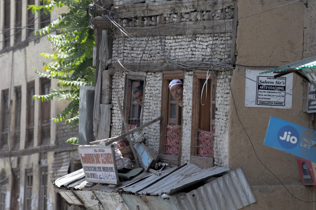 Kashmiri men watch from the window of their house near the site of a gun battle in Srinagar, Indian controlled Kashmir, Tuesday, May 19, 2020. Indian ...