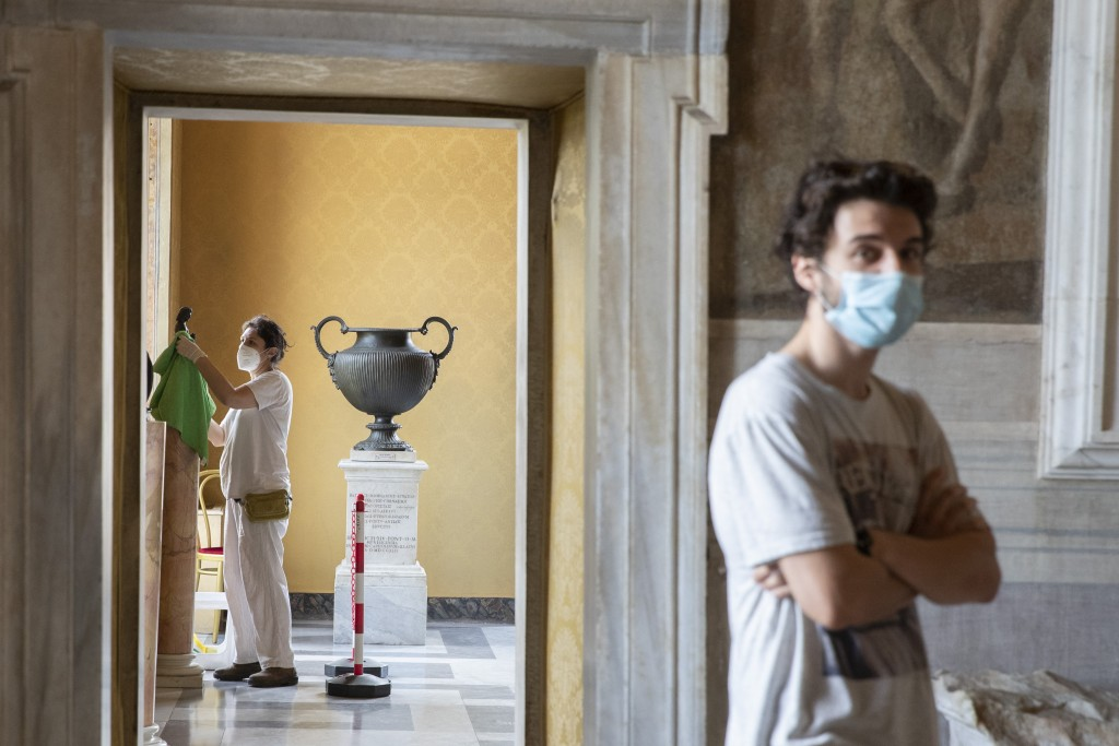 A museum employee cleans a statue, as a visitor wearing face mask to prevent the spread of COVID-19 walks in the Rome's Capitoline Museums, Tuesday, M...