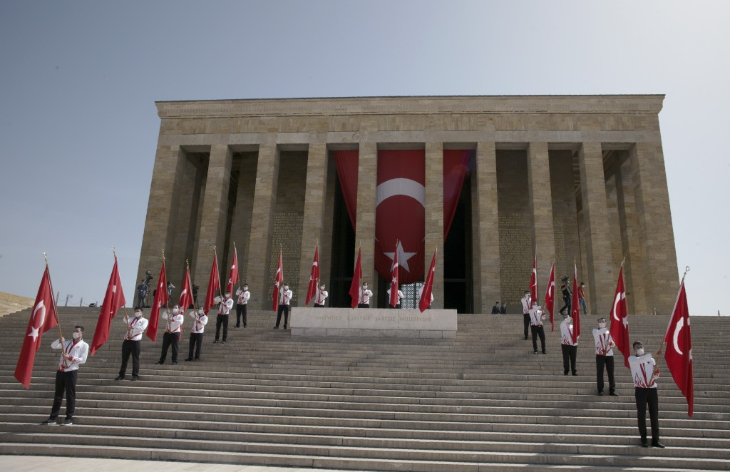 Turkish students wearing face masks for protection against the new coronavirus, wave national flags during a ceremeny at the mausoleum of Mustafa Kema...