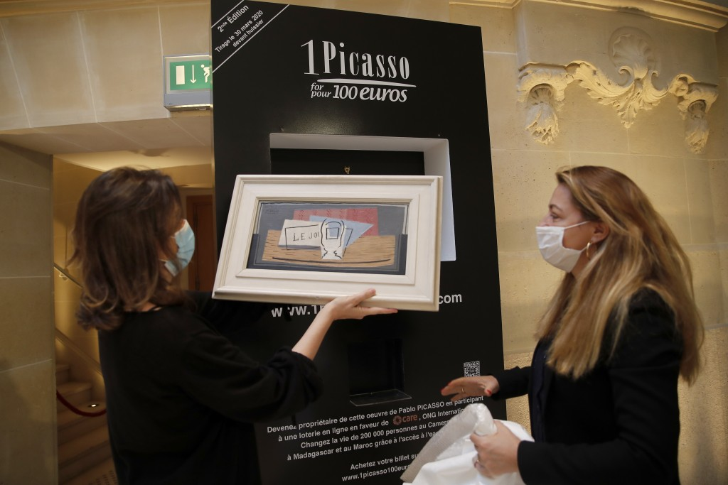 """Raffle organizers Peri Cochin, left, and Arabenne Reille put the painting """"Nature morte"""" by Picasso in its frame at Christie's auction house, Tuesday,..."""
