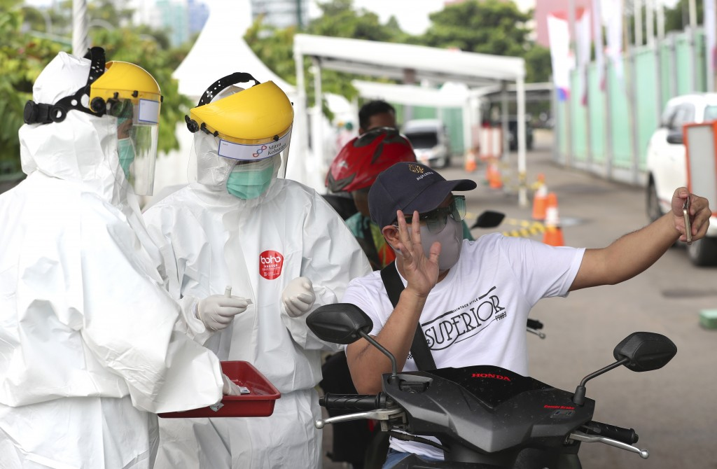 A man makes video call before a health worker takes his blood sample for a new coronavirus rapid test in Bekasi on the outskirts of Jakarta, Indonesia...