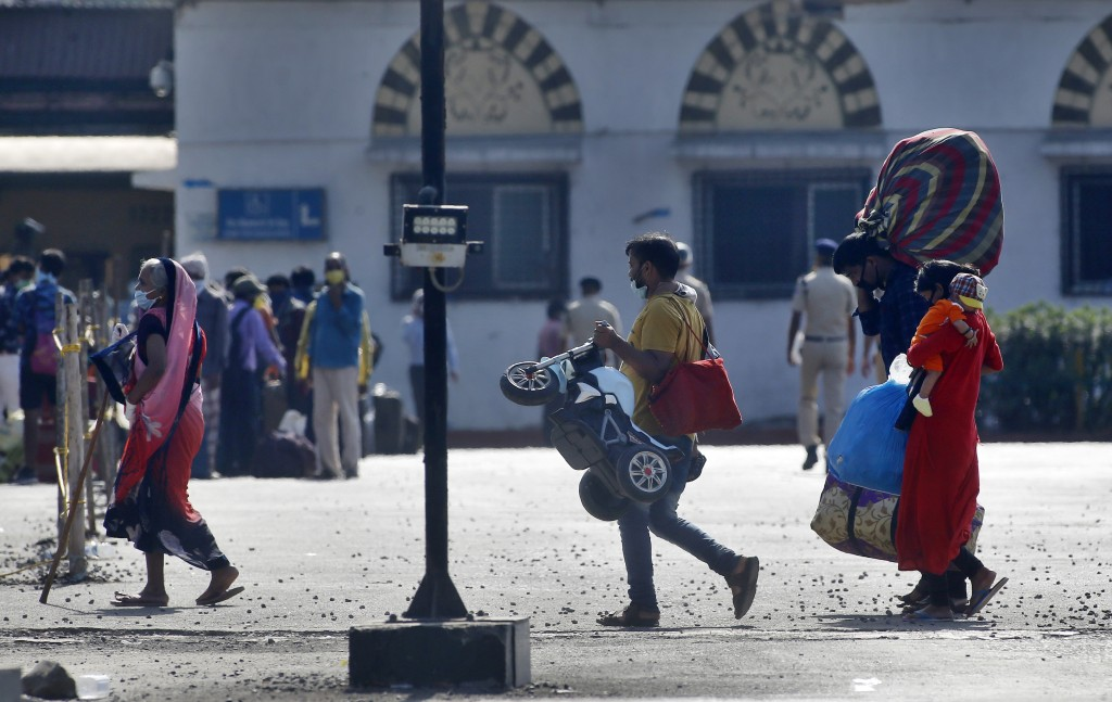 People from other states trying to get back to their homes arrive to board trains at the Chhatrapati Shivaji Maharaj Terminus in Mumbai, India, Tuesda...