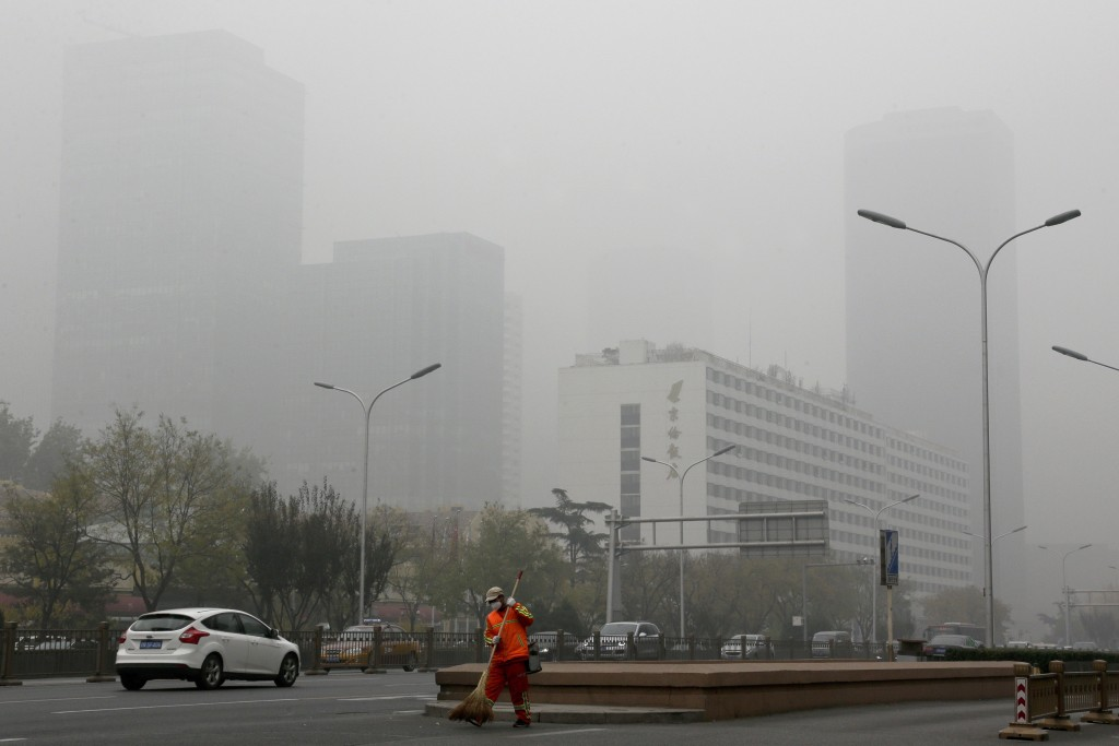 FILE - In this Nov. 14, 2018, file photo, a cleaner wearing a mask against pollution sweeps a street in Beijing. The world cut its daily carbon dioxid...