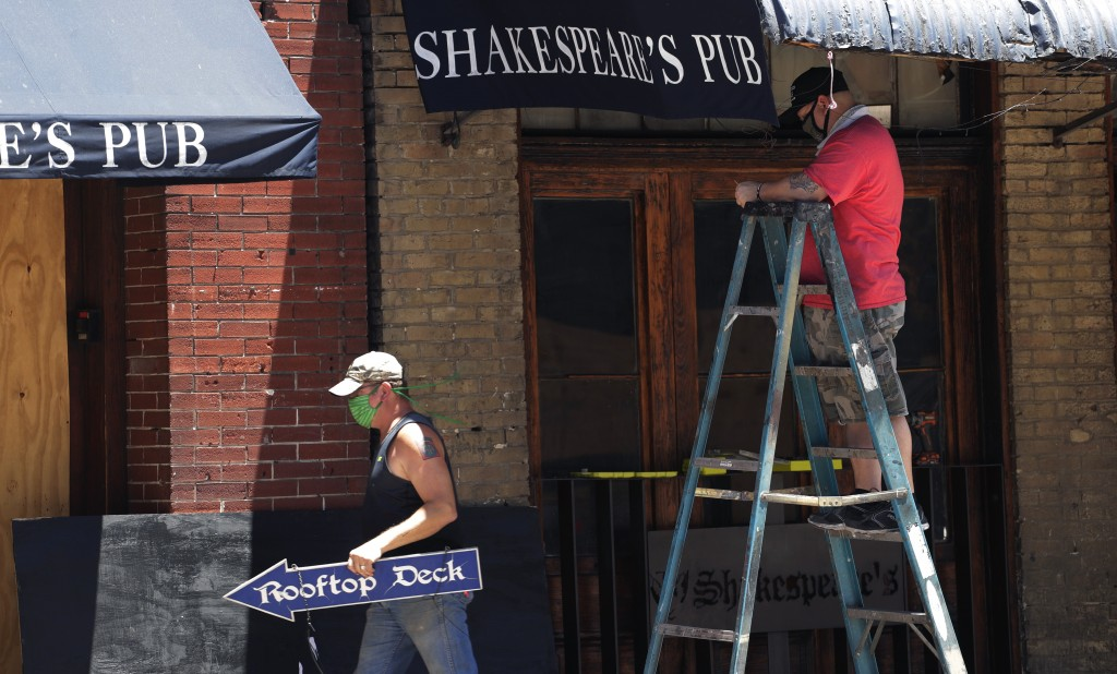 Workers who only gave their first names, Joe, left, and Danny, right, work to prepare their pub that they hope to reopen soon in Austin, Texas, Monday...
