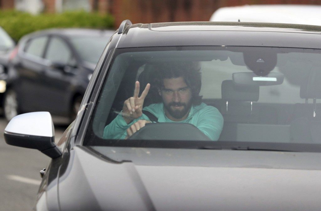 Liverpool's goalkeeper Alisson gestures as he arrives at the club's Melwood training ground after the English Premier League announced soccer players ...