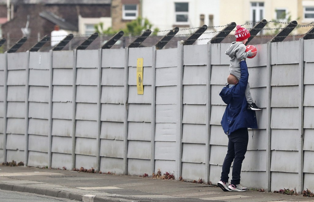 A man holds a child up over a fence to look into Liverpool's Melwood training ground after the English Premier League announced soccer players can ret...