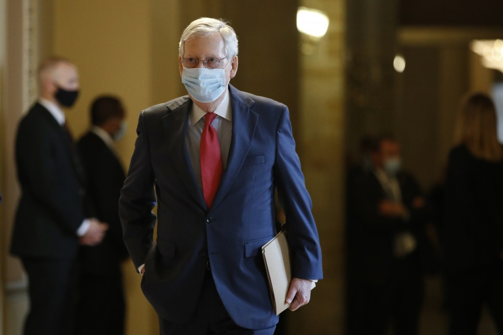 Senate Majority Leader Mitch McConnell of Ky., wears a face mask to protect against the spread of the new coronavirus as he walks to the Senate chambe...