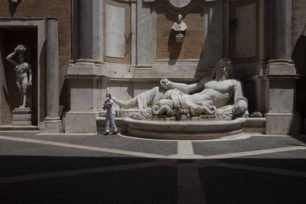 A museum employee wearing a face mask to prevent the spread of COVID-19 fills a bottle at a fountain next to the 3rd century marble statue known as Ma...