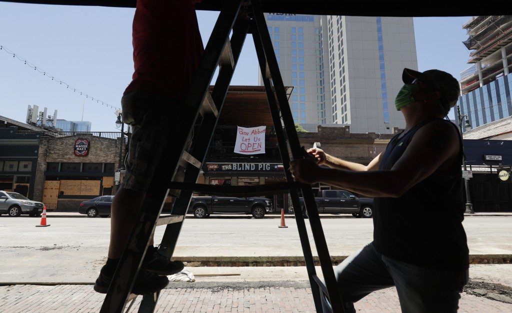 A sign directed at Texas Gov. Greg Abbott is seen behind workers preparing another pub that they hope to reopen soon in Austin, Texas, Monday, May 18,...