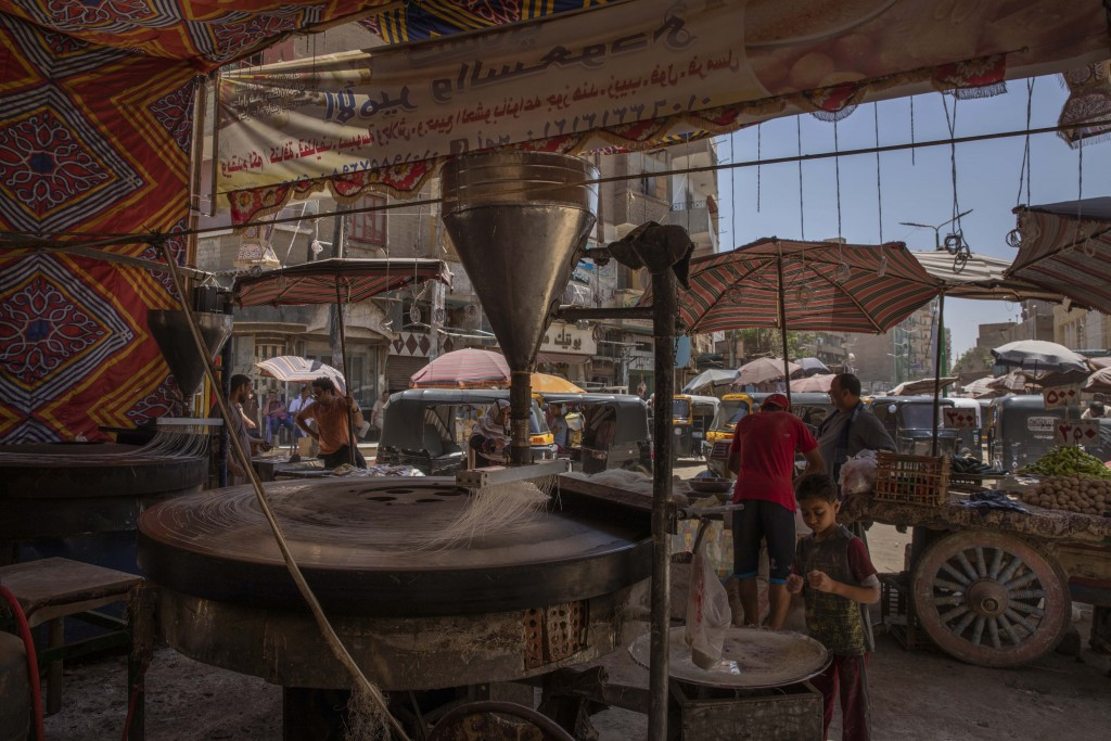 This May 9, 2020 photo, shows the Ramadan sweets shop where 28-year-old football defender Mahrous Mahmoud works at a market, in Manfalut, a town 350 k...