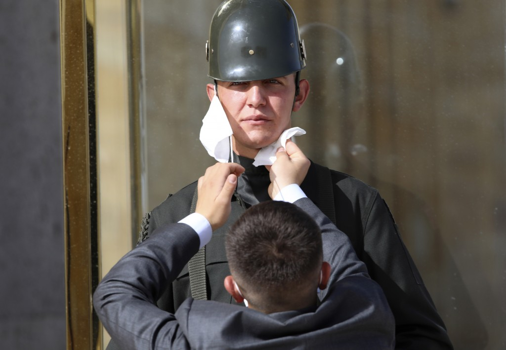 A man wipes the face of a Turkish soldier wearing a face mask for protection against the new coronavirus, before a ceremony at the mausoleum of Mustaf...