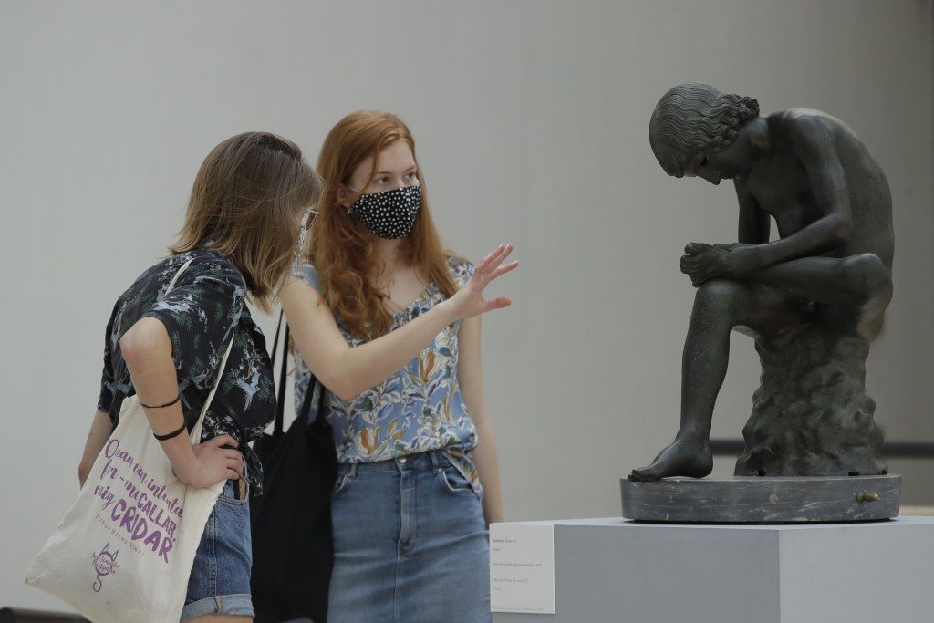 "Visitors wearing face mask to prevent the spread of COVID-19, look at 'The Boy with Thorn"" a first century B.C. bronze statue in the Rome's Capitoline..."