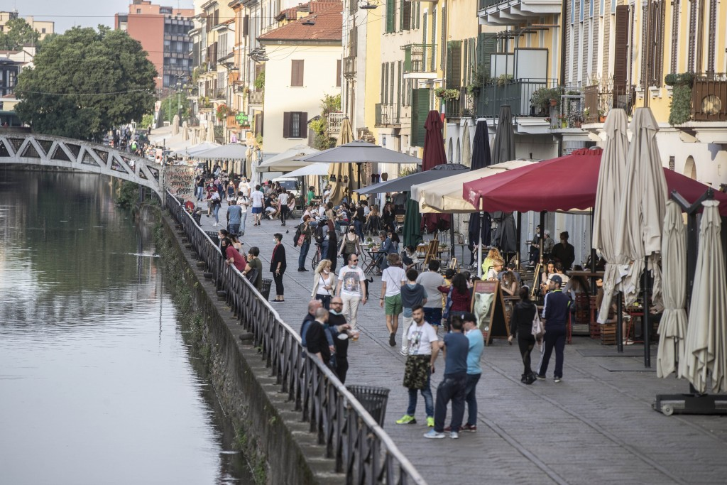 People walk at the Naviglio grande canal district in Milan, Italy, Monday, May 18, 2020. On Monday, Italians enjoyed a first day of regained freedoms,...