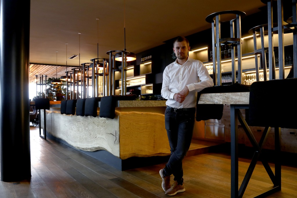In this picture taken on Wednesday, May 13, 2020, restaurant employee Patrick Lanziner poses in front of his bar at the My Arbor wellness hotel in Bre...