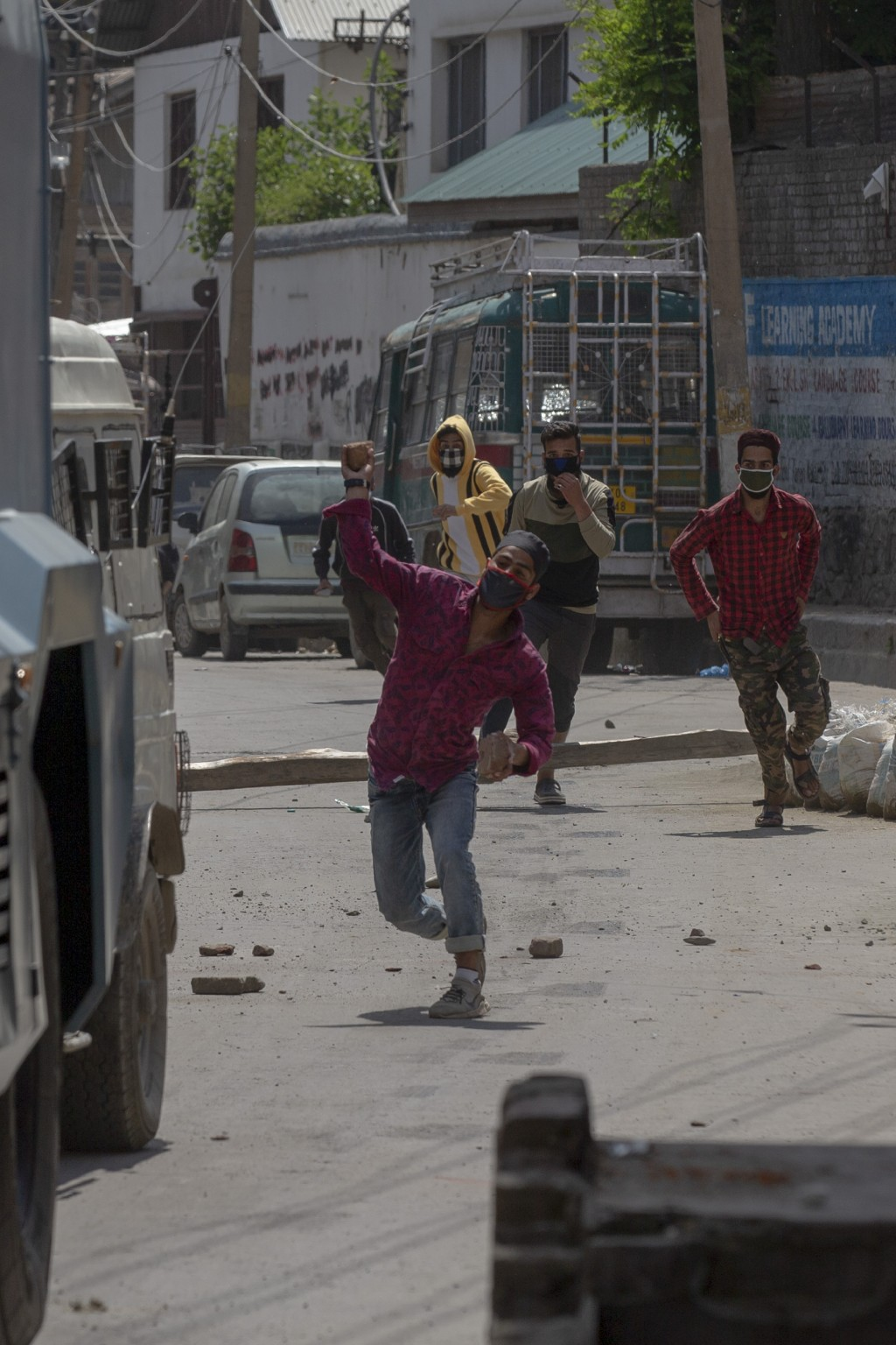 Kashmiri men throw rocks and bricks at vehicles belonging to Indian paramilitary soldiers as they leave the site of gun battle in Srinagar, Indian con...