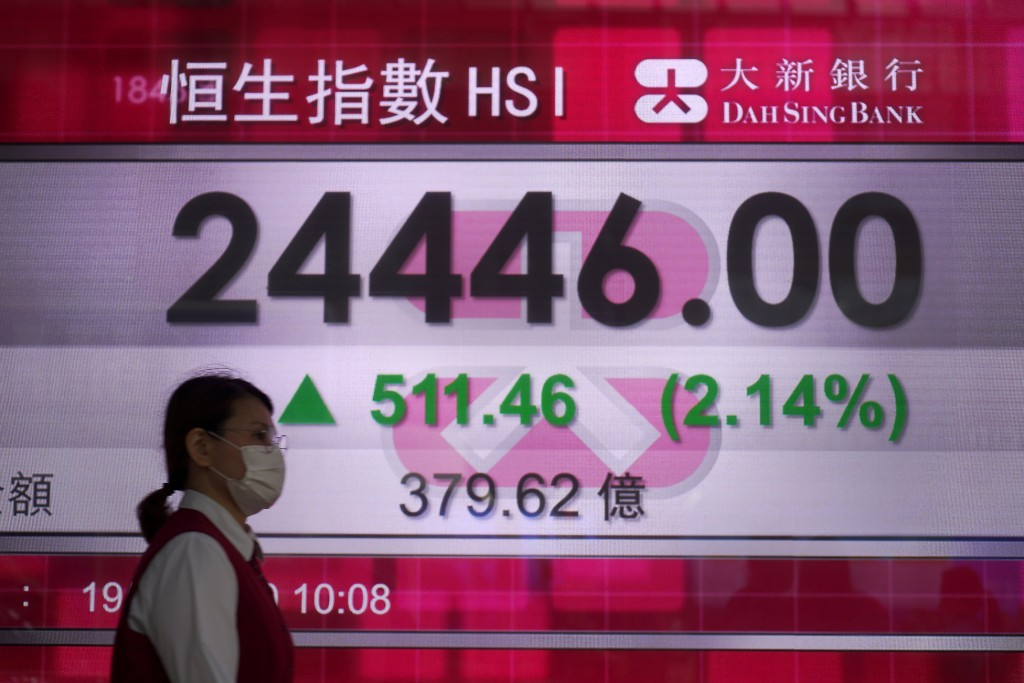 A woman wearing face mask walks past a bank electronic board showing the Hong Kong share index Tuesday, May 19, 2020. Asian shares rose Tuesday on opt...