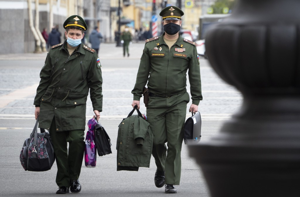 Russian army officers wearing face masks to protect against coronavirus walk in St.Petersburg, Russia, Tuesday, May 19, 2020. Russia has continued to ...