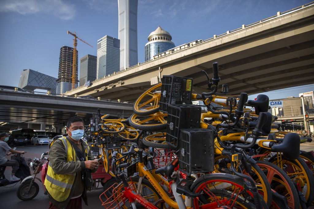 A worker wearing a face mask to protect against the new coronavirus places shared bicycles onto a cart in the central business district in Beijing, Tu...