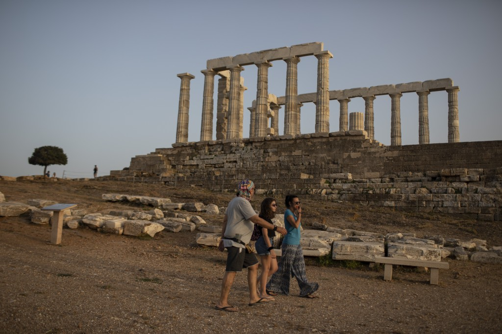 Visitors walk past the 444 BC ancient marble temple of Poseido , at Cape Sounion, south of Athens on Monday May 18, 2020. Greece reopened the Acropoli...