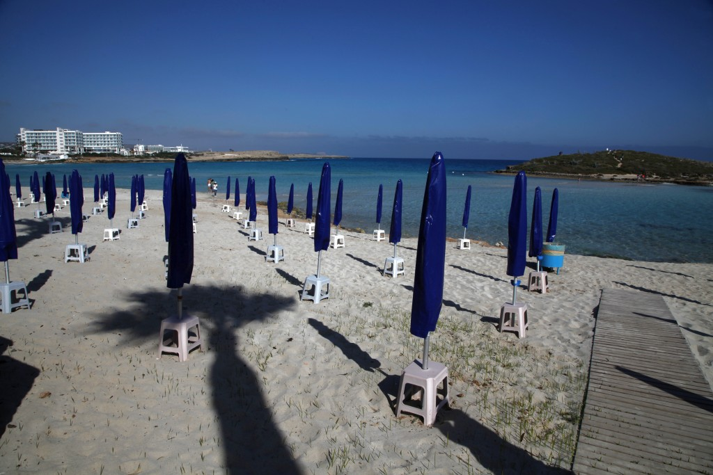 "In this photo taken on Sunday, May 10, 2020, people walk among folded beach umbrellas dotted on an empty stretch of ""Nissi beach"" in Ayia Napa, Cyprus..."