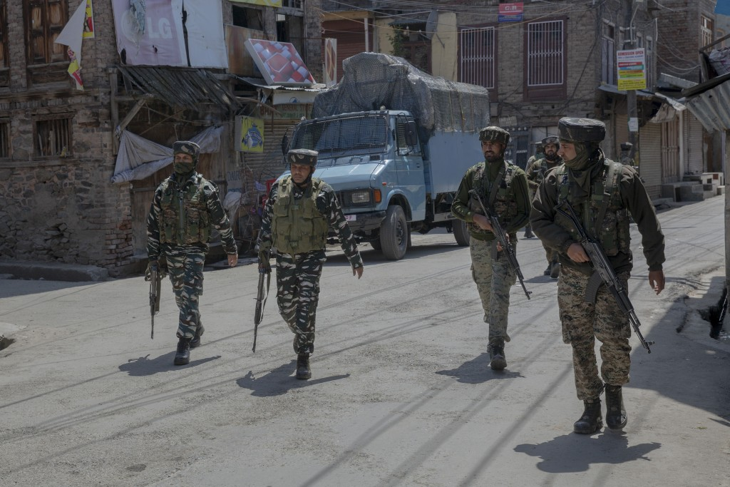 Indian paramilitary soldiers walk back towards their vehicles after a gun battle with suspected rebels ended in Srinagar, Indian controlled Kashmir, T...