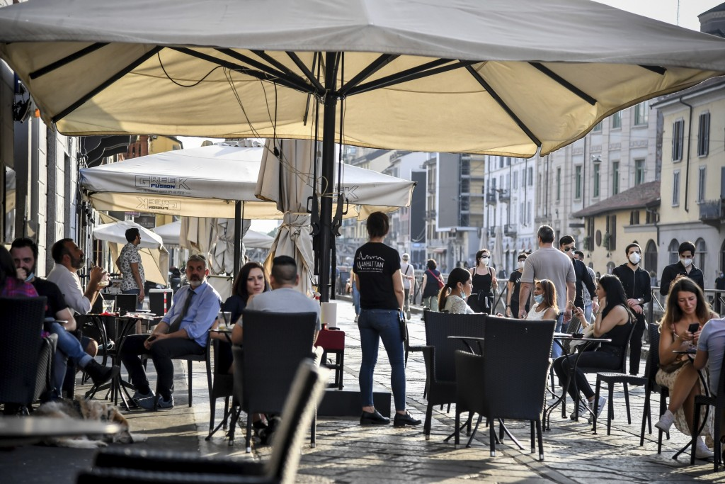 People sit at a cafe in Milan, Italy, Monday, May 18, 2020. On Monday, Italians enjoyed a first day of regained freedoms, including being able to sit ...
