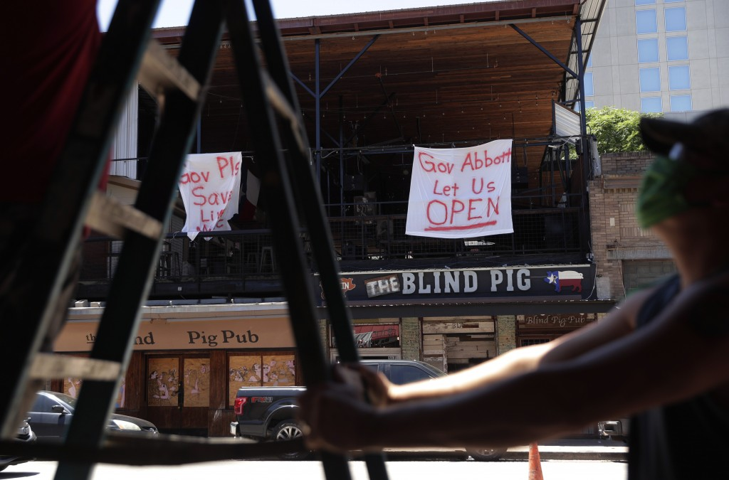Signs directed at Texas Gov. Greg Abbott are seen behind workers preparing another pub that they hope to reopen soon, in Austin, Texas, Monday, May 18...