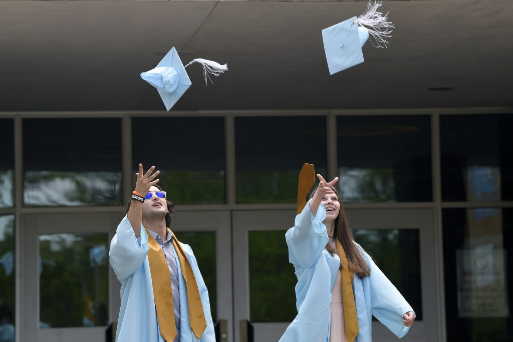 South River High School seniors Sam Peterson, left, and his cousin Harley Snead, right, both from Edgewater, Md., toss their caps for a photo shoot wi...