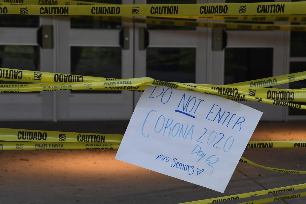 A sign hangs outside the South River High School in Edgewater, Md., Wednesday, May 13, 2020, after a groups of seniors decorated the school in caution...
