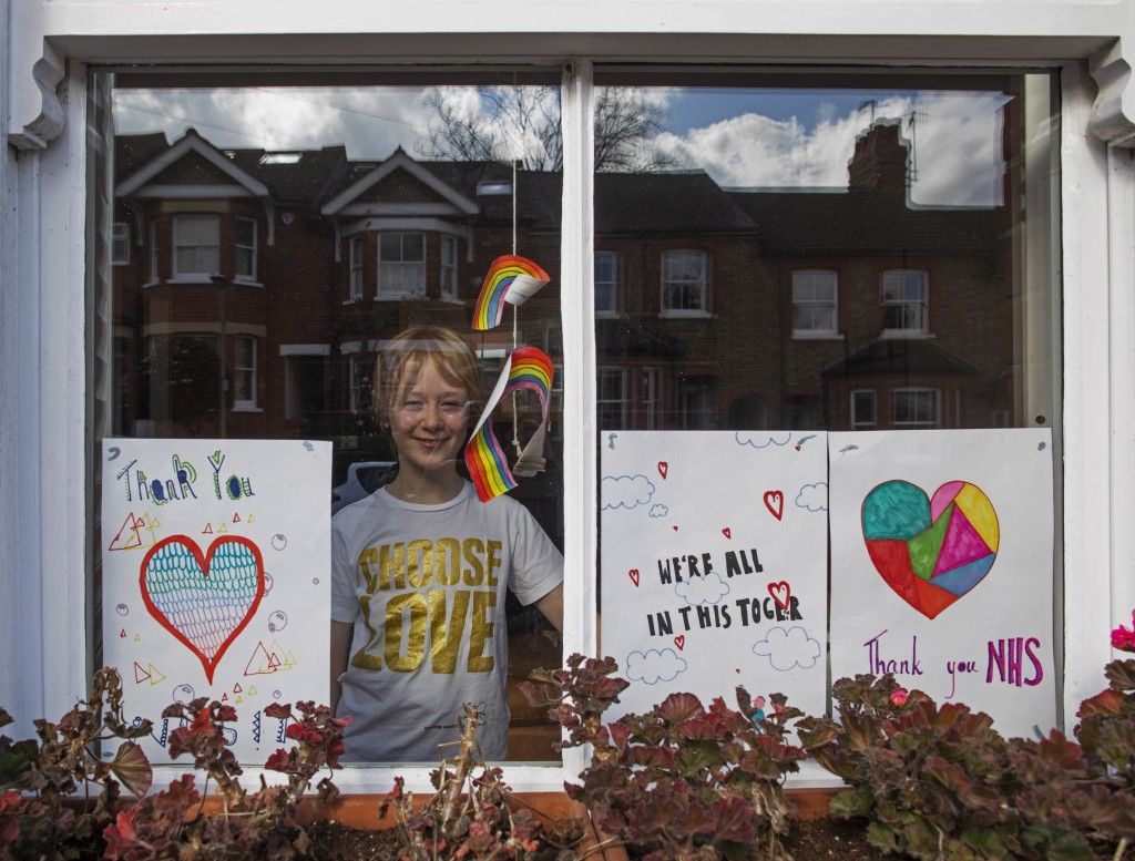 Ellie Davis looks out from her living room window surrounded by posters she made to thank the National Health Service in Berkhamsted, England, Tuesday...