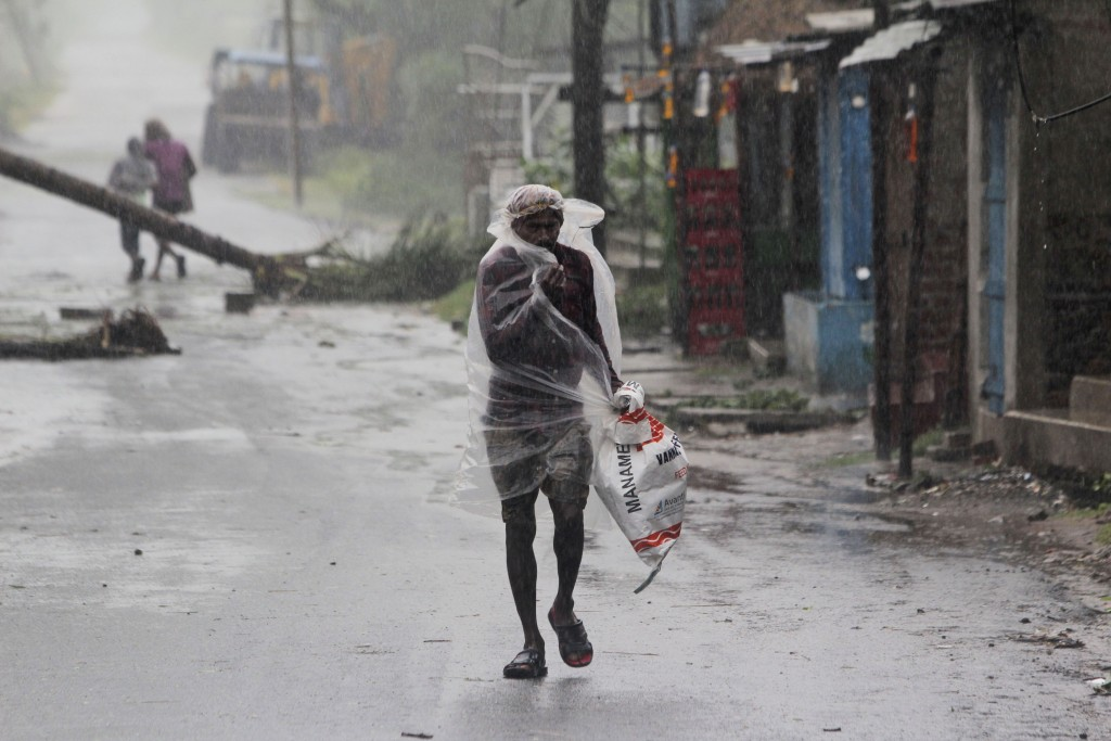 A man covers himself with a plastic sheet and walks in the rain ahead of Cyclone Amphan landfall, at Bhadrak district, in the eastern Indian state of ...