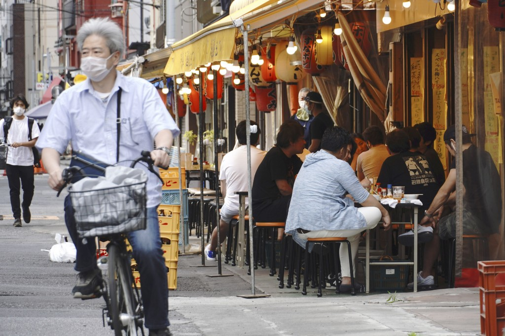 People have drink at a bar along a street in Tokyo Friday, May 15, 2020. While Tokyo is still under a coronavirus state of emergency, the pandemic is ...