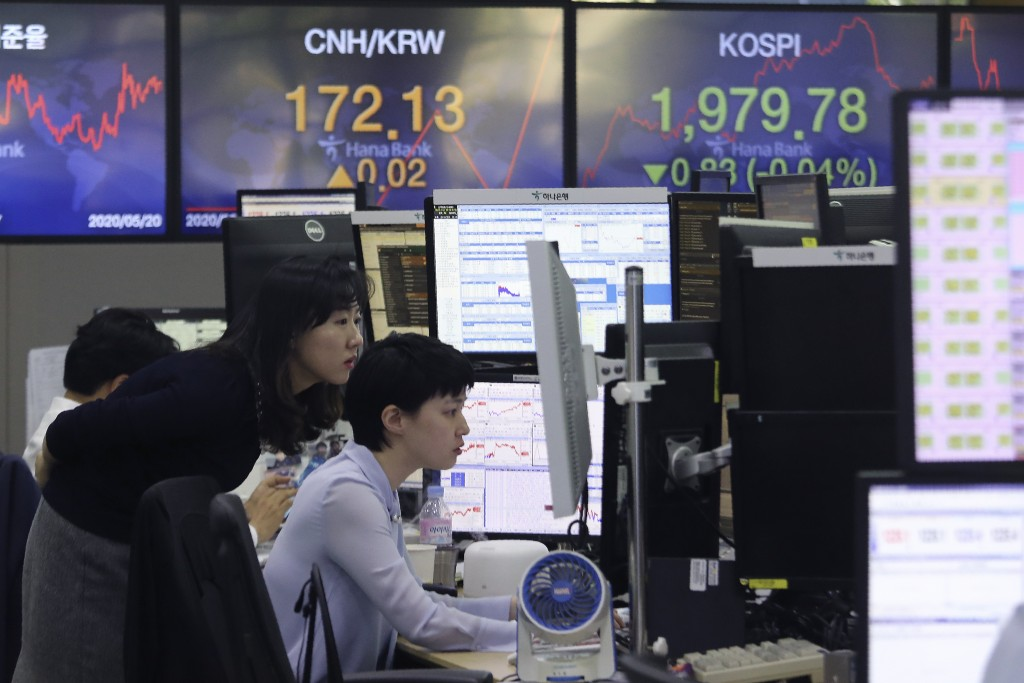 Currency traders watch monitors at the foreign exchange dealing room of the KEB Hana Bank headquarters in Seoul, South Korea, Wednesday, May 20, 2020....