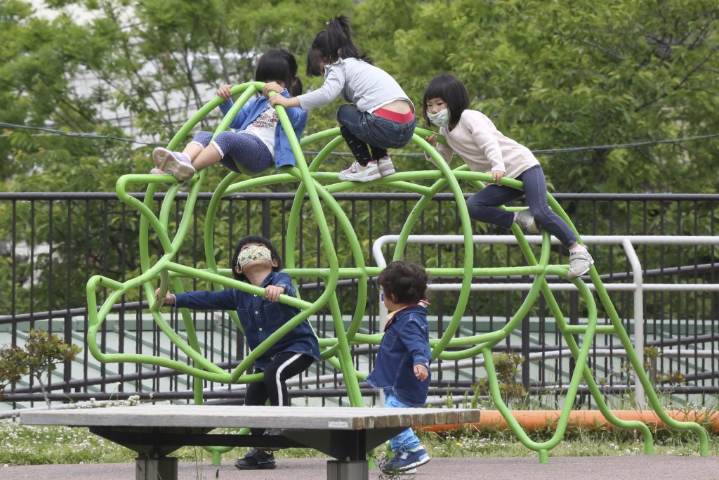 Children wearing face masks to protect against the spread of the new coronavirus play at a park in Yokohama, Kanagawa prefecture, near Tokyo, Wednesda...