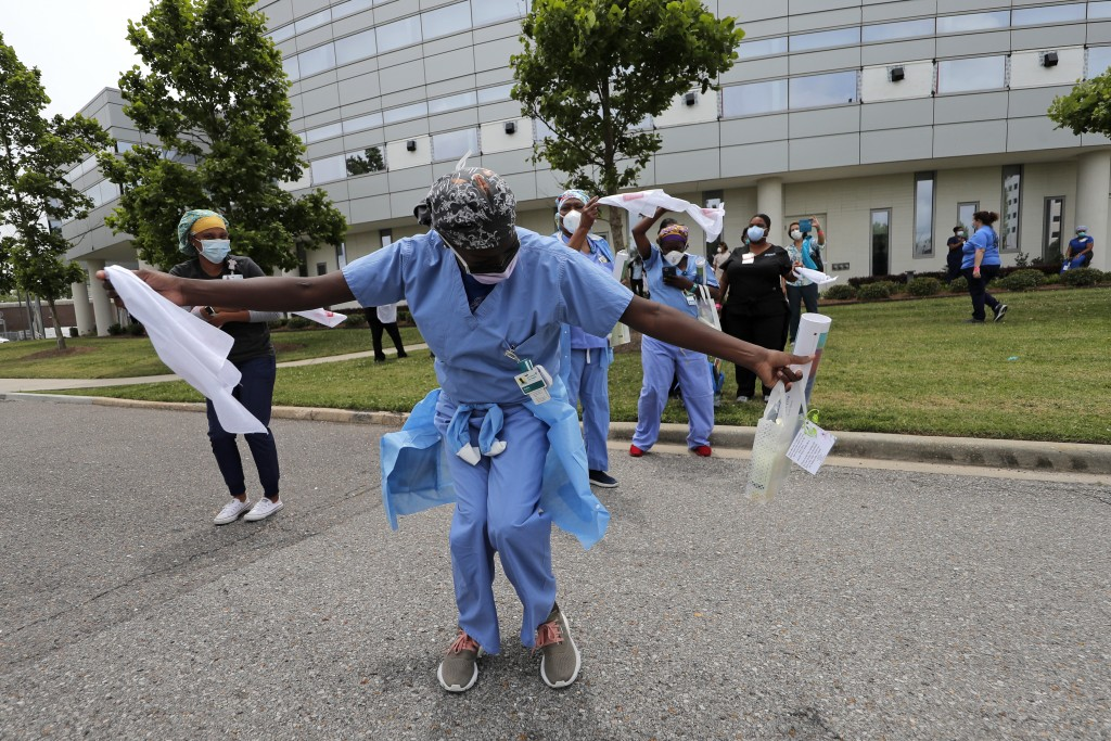 Healthcare workers at New Orleans East Hospital wave handkerchiefs and dance to a jazz serenade, as a tribute for their care of COVID-19 patients, by ...