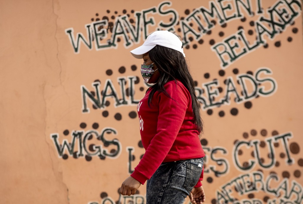 A woman wearing a face mask to protect herself against coronavirus, walks past a closed hair salon at Tembisa township in Johannesburg, South Africa, ...