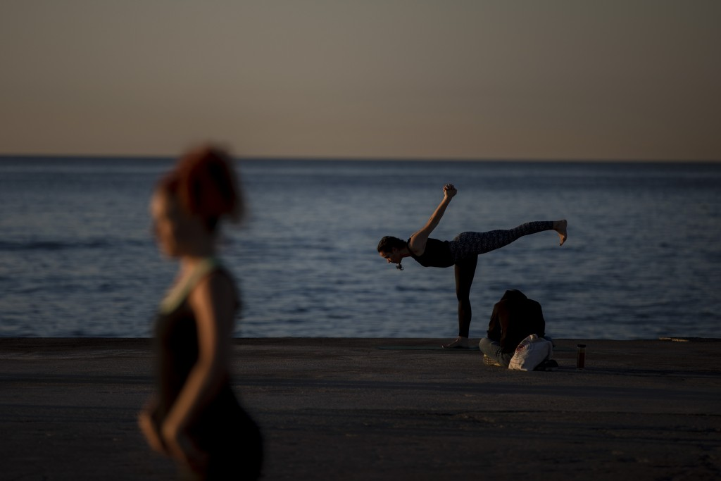 People exercise in front of sea in Barcelona, Spain, Wednesday, May 20, 2020. Barcelona allowed people to walk on its beaches Wednesday, for the first...