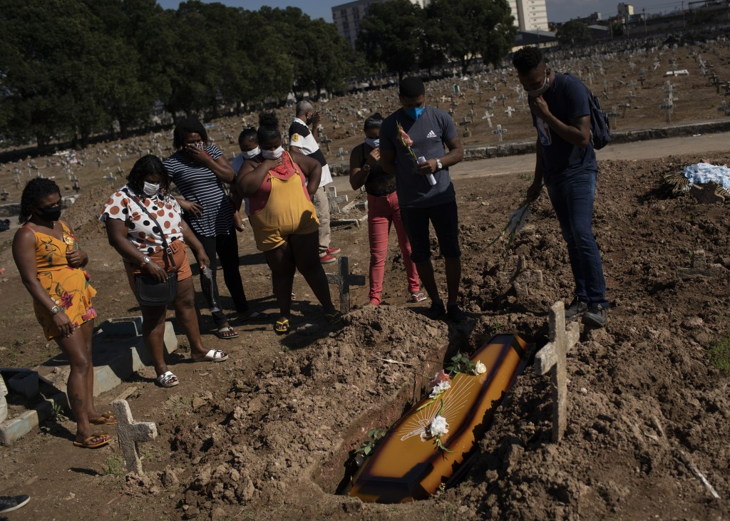 Relatives attend the burial of Vandelma Rosa de Almeida, 66, whose death certificate states is suspected of having died of COVID-19, at the Caju cemet...