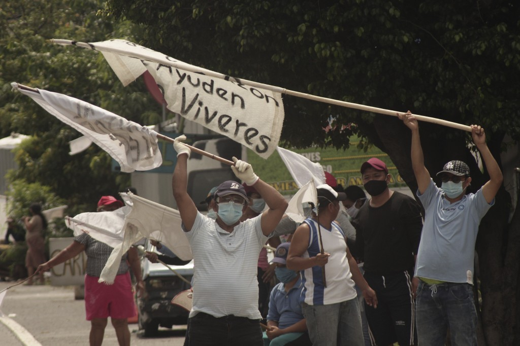 People raise white flags begging for food from drivers on the Golden Highway in Ilopango, El Salvador, Tuesday, May 19, 2020. Poor Salvadorans who hav...