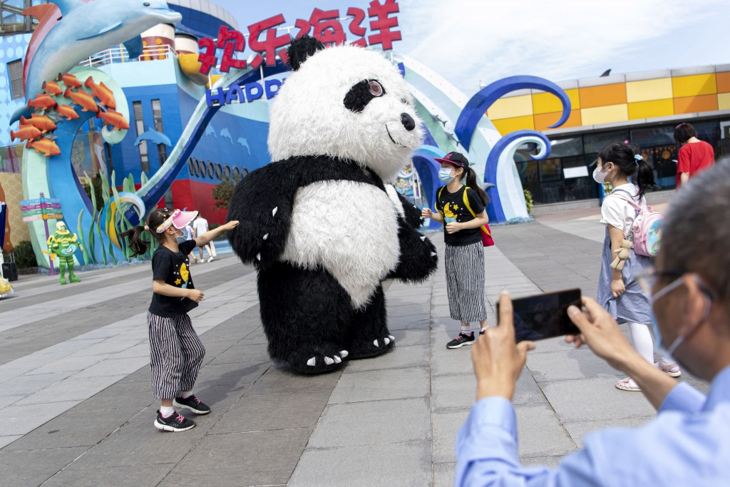 In this, Tuesday, May 19, 2020, photo released by Xinhua News Agency, tourists wearing mask sas precaution against the coronavirus pose for photos wit...