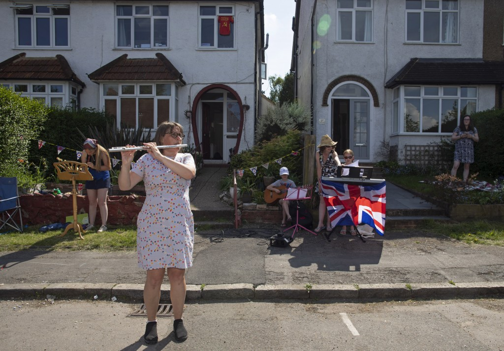 Nyree O'Brien, a music teacher and neighbor plays the flute as she directs a socially distant concert during Victory in Europe Day in Berkhamsted, Eng...