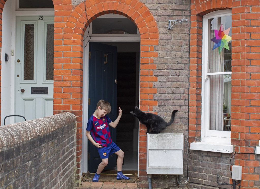 Isaac Skelding stands outside his front door as the neighbor's cat looks inside his house in Berkhamsted, England, Wednesday, April 1, 2020. Isaac who...