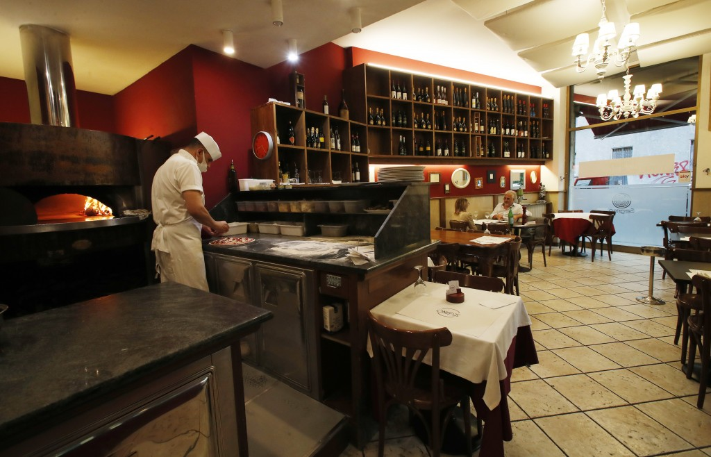 "In this photo taken on Tuesday, May 19, 2020, a cook prepares a pizza as a two customers sit at a table, at the ""La Rotonda di Segrino"" restaurant in ..."