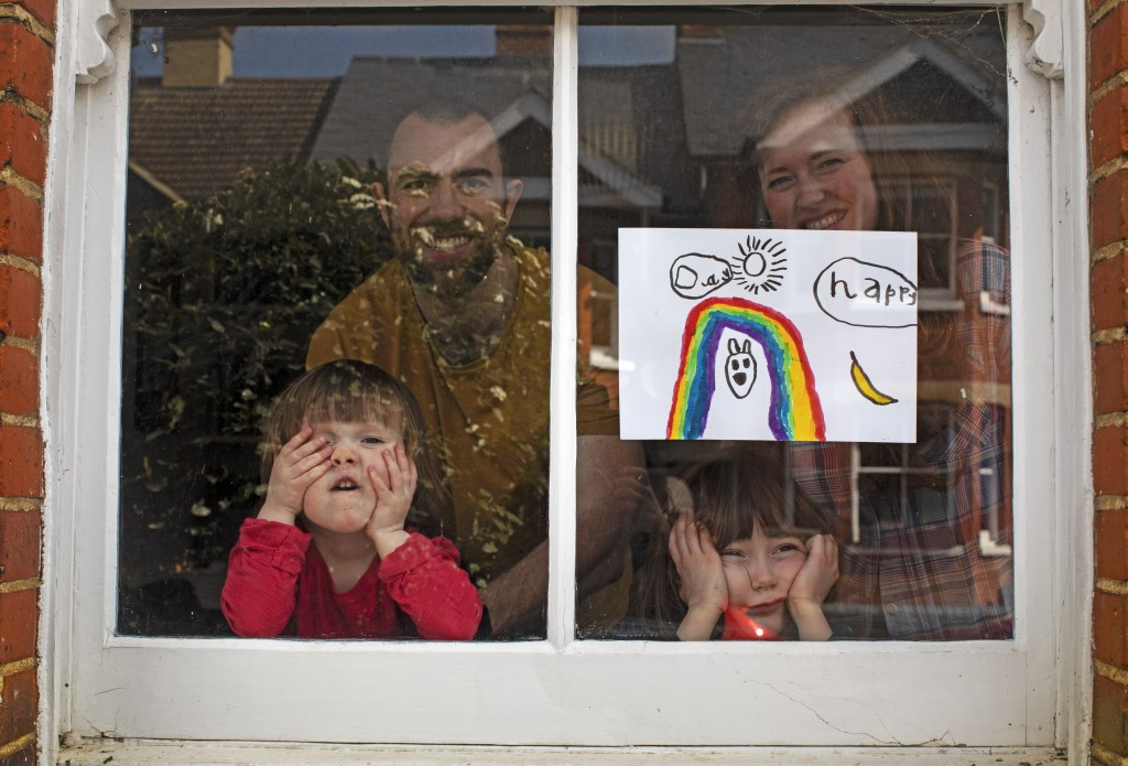 Amelie and her sister Camille watch from their front window as the lockdown enters it's third week along with their parents Victoria and Damian Kerr i...