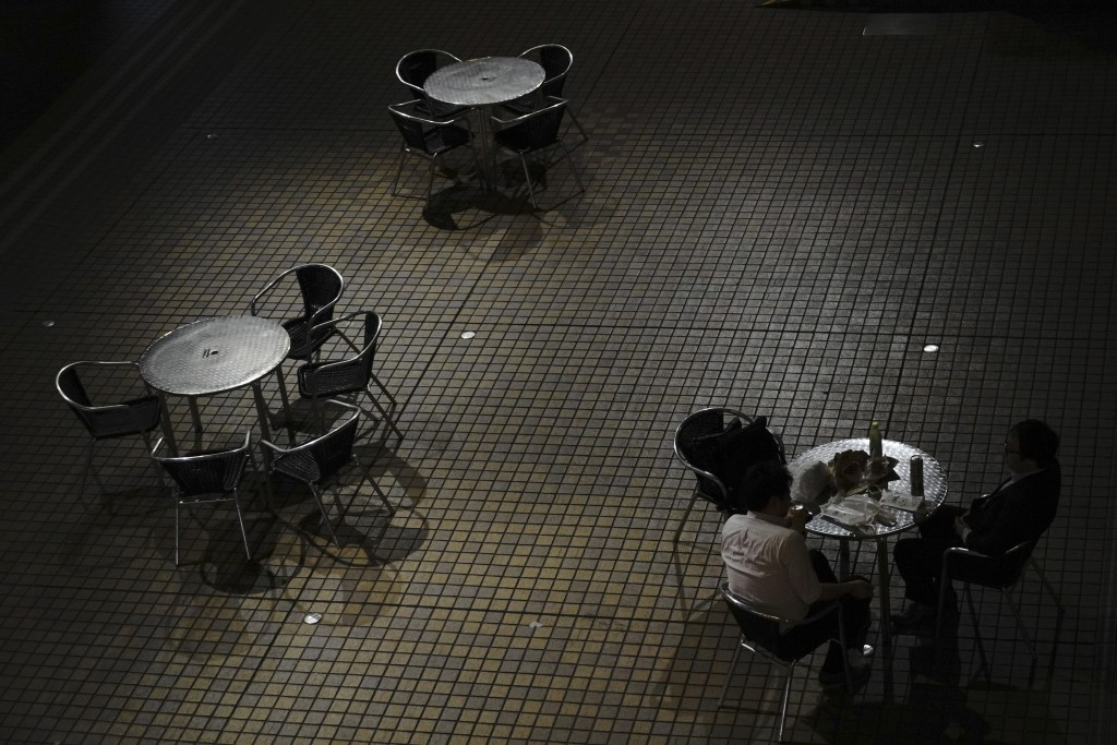 Men chat while drinking at an empty courtyard at a business district in Tokyo Thursday, May 14, 2020. While Tokyo is still under a coronavirus state o...