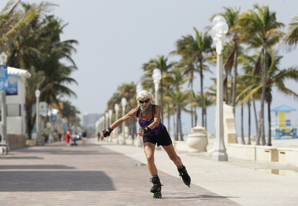 A rollerblader skates on the Broadwalk on Hollywood beach, Tuesday, May 19, 2020, in Hollywood, Fla. Broward County started a phased reopening Monday....