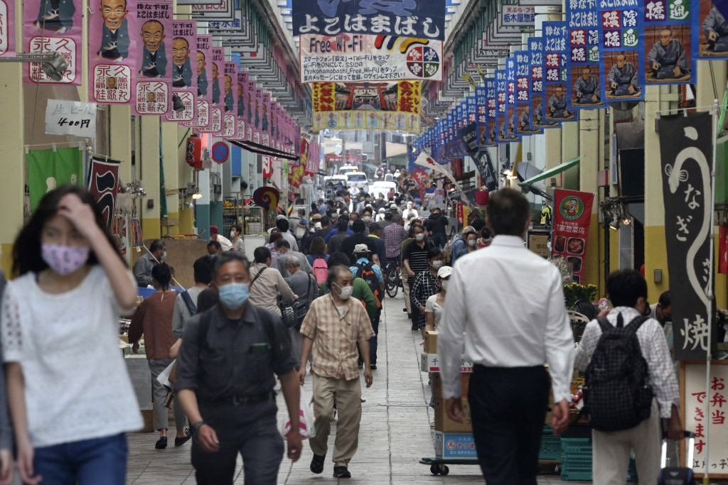 People wearing face masks to protect against the spread of the new coronavirus enjoy shopping in Yokohama, Kanagawa prefecture, near Tokyo, Wednesday,...