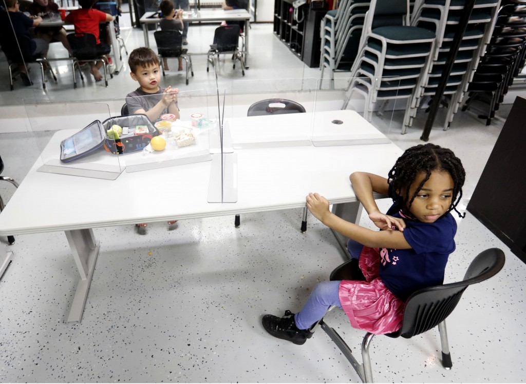 Plastic barriers are placed between Bruce McCall, 5, left, and Capri Bishop, 6, as they sit at a table during martial arts daycare summer camp at Lege...